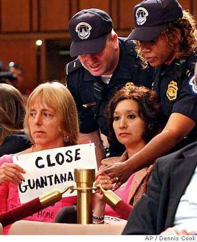 "Capitol Police officers talk to Medea Benjamin, left, and Nancy Mancias, both from San Francisco, Calif., and carrying signs saying ""Close Guantanamo"", after they created disturbance during a Senate Judiciary Committee hearing on detainee and enemy combatant legal rights on Capitol Hill in Washington Tuesday, July 11, 2006. (AP Photo/Dennis Cook) Photo: DENNIS COOK"
