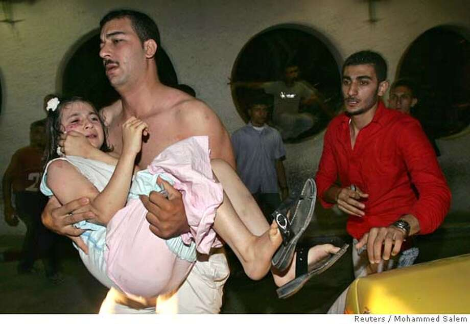 A Palestinian man carries a wounded girl to the hospital after Israeli aircraft fired a missile at a car in Gaza July 9, 2006, blowing it up and wounding five people, witnesses and medics said. REUTERS/Mohammed Salem (PALESTINIAN TERRITORIES)  Ran on: 07-10-2006  A girl is carried to the hospital after an Israeli missile hit a car in Gaza, blowing it up and injuring five people, witnesses and medics said. Photo: MOHAMMED SALEM