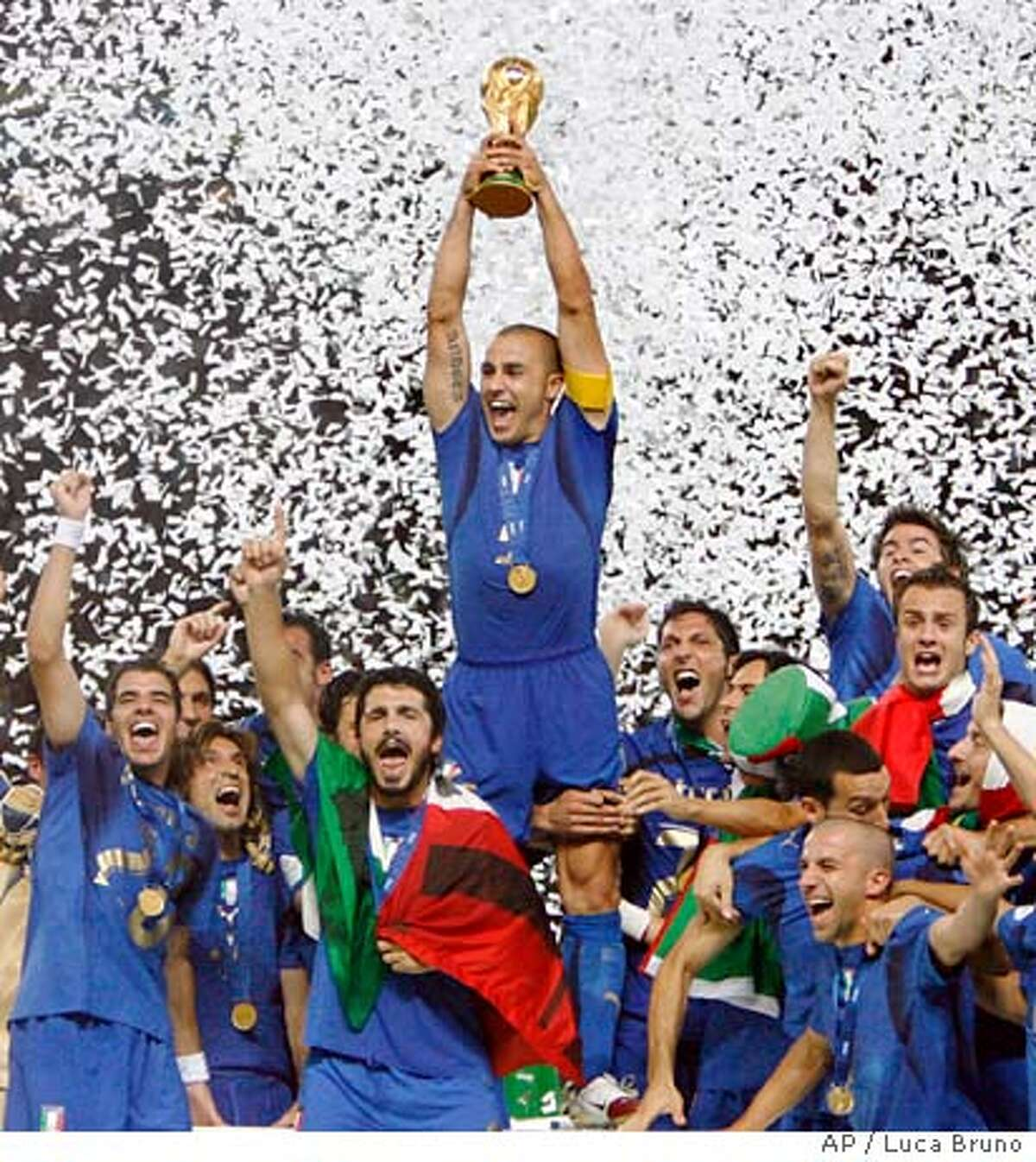 Italy's team captain Fabio Cannavaro holds aloft the World Cup trophy surrounded by teammates after the final of the soccer World Cup between Italy and France in the Olympic Stadium in Berlin, Sunday, July 9, 2006. Italy defeated France 5-3 in a shootout after a 1-1 draw. (AP Photo/Luca Bruno) ** MOBILE/PDA USAGE OUT **