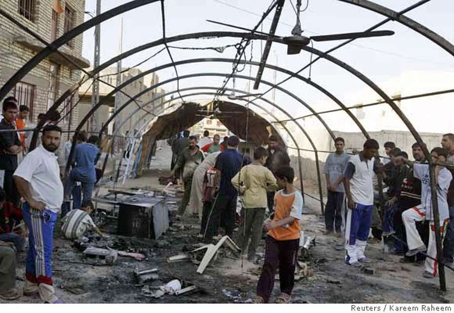 Residents gather under a destroyed funeral tent, after clashes between members of the Mehdi army against U.S. troops in Baghdad's Sadr city July 7, 2006. At least seven people were killed in clashes between U.S.-led troops and the Mehdi Army militia of Shi'ite cleric Moqtada al-Sadr in eastern Baghdad early on Friday, police and witnesses said. REUTERS/Kareem Raheem (IRAQ)  Ran on: 07-08-2006  Residents gather under a destroyed funeral tent after a firefight in the Sadr City slum of Baghdad. Photo: KAREEM RAHEEM