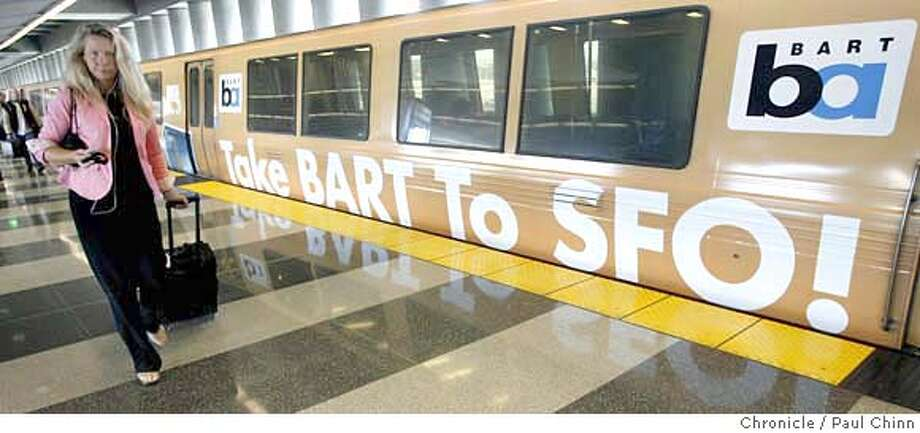A traveler arriving at the SFO station walks past a BART car wrapped with an ad promoting the direct service to San Francisco International Airport in San Francisco, Calif. on Friday, July 7, 2006. Fewer riders are taking advantage of the service than BART officials had hoped for when the service began three years ago despite the convenience of BART's station directly inside the international terminal. PAUL CHINN/The Chronicle Photo: PAUL CHINN