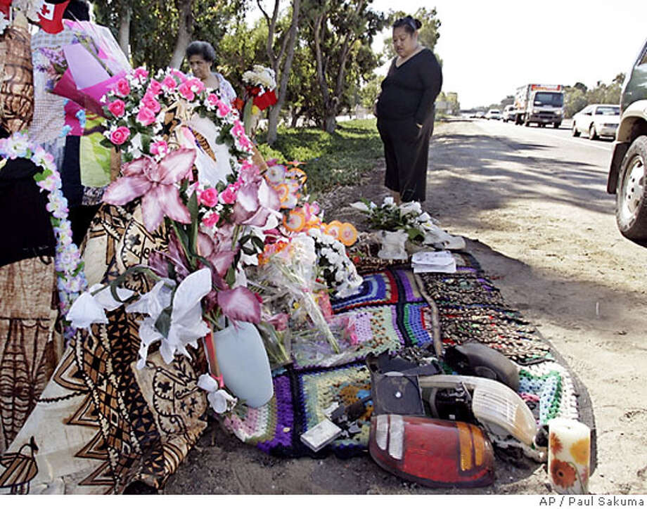 Parts of a crashed vehicle is displayed at a make-shift memorial Friday, July 7, 2006 at the site of a crash that killed two members of Tonga's royal family, Prince Tu'ipelehake, 56, and his wife, Princess Kaimana, 46 and their driver, Vinisia Hefa . They were killed when a teenager racing her car crashed into their vehicle on Wednesday, July 5, 2006. (AP Photo/Paul Sakuma) Photo: PAUL SAKUMA