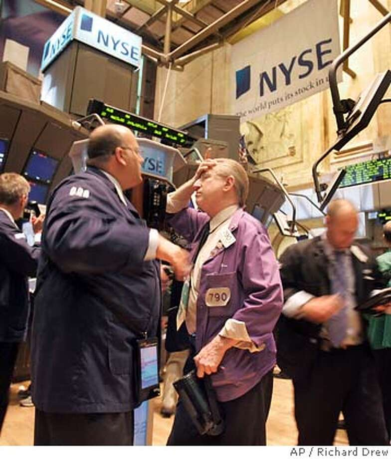 *** FILE ** Traders meet at a phone post on the floor of the New York Stock Exchange, June 6, 2006, as stocks sagged in early trading after comments by Federal Reserve (Fed) Chairman Ben Bernanke the day before sparked a sell off, which reverberated globally. Wall Street reacted strongly again on June 29 with the biggest single-day jump in more than three years, following a statement issued by Fed policymakers. (AP Photo/Richard Drew, File) JUNE 6, 2006 FILE PHOTO Photo: RICHARD DREW