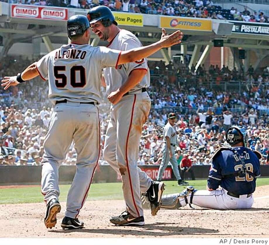 San Francisco Giants' Matt Morris, center, is congratulated by the Giants' Eliezer Alfonzo, left, as San Diego Padres catcher Josh Bard, right, looks out to the field after Morris scored on hit by the Giants Omar Vizquel in seventh inning of their baseball game Sunday, July 2, 2006 in San Diego. The Giants won 6-2. (AP Photo/Denis Poroy) Photo: DENIS POROY
