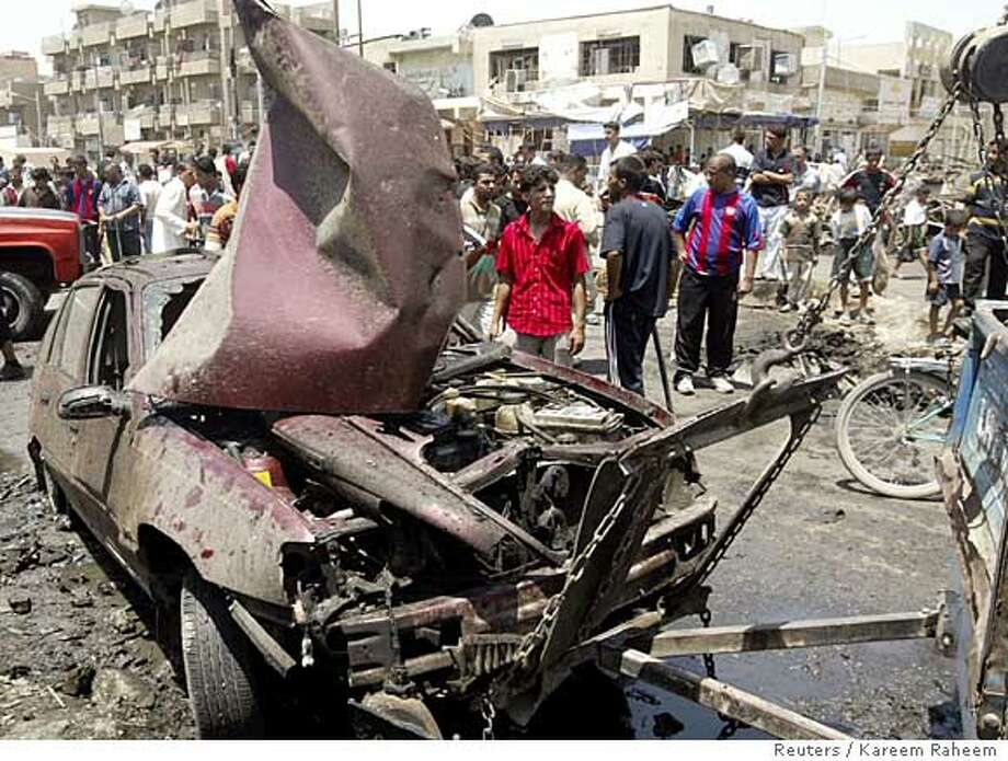 A damaged car is towed from the scene of a car bomb attack in a market in Baghdad's Sadr city Photo: KAREEM RAHEEM