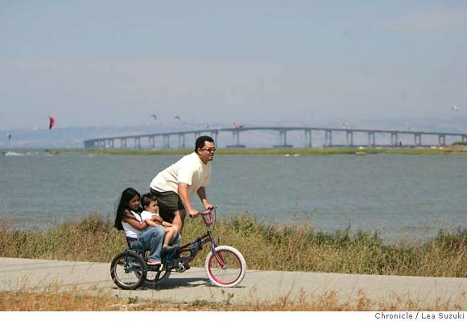 july4roundup_074_ls.JPG  From left: Malia Manuel of San Francisco; Rory Manalo 2 and 1/2 of Daly City and his father Ramil Manalo of Daly City. Ramil Manalo rides along the Bay Trail down in San Mateo off of Seal Point Park while Maneul and son, Rory, enjoy the ride from the side seat. The San Mateo Bridge is in the background.  People enjoy the Bay Trail down in San Mateo off of Clinton Drive on Sunday June 25, 2006.  Photo by Lea Suzuki/The San Francisco Chronicle  Photo taken on 6/25/06, in San Mateo, CA. **Malia Manuel(Malia Manuel); Rory Manalo, Ramil Manalo(Ramil Manalo) cq. MANDATORY CREDIT FOR PHOTOG AND SAN FRANCISCO CHRONICLE/ -MAGS OUT Photo: Lea Suzuki