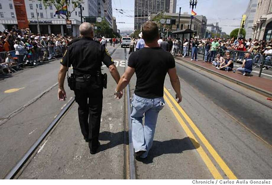 prideparade26006_cag.jpg  Partners Kevin Heuer, left, and Todd Leichleiter, march down Market Street in San Francisco during the 36th Annual Gay Pride Parade on Sunday, June 25, 2006. Photographed in San Francisico  Carlos Avila Gonzalez/The Chronicle MANDATORY CREDIT FOR PHOTOG / Photo: Carlos Avila Gonzalez