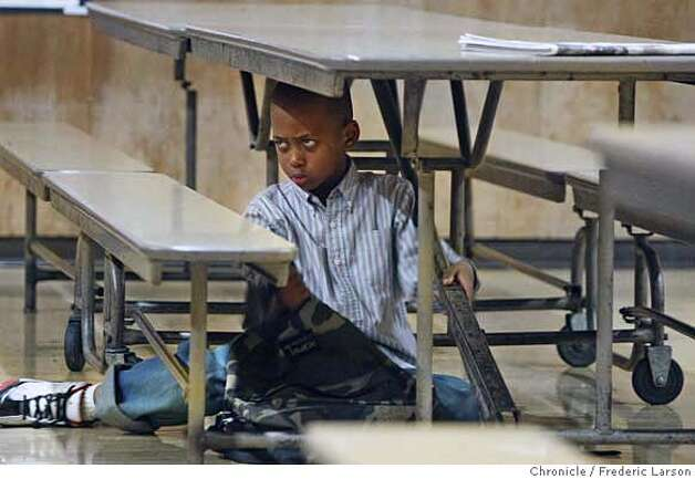 Charles Hollins, 1st grader, age 6 from MalcolmX Elementary is not having a good morning as he find sitting under a table the spot that offers comfort. Last night (Thursday 1/12) the school board did not decided the fate of Malcolmx Academy on weather the doors will stay open for another year and the mood the morning after when from haggard to seer exhaustion. The vote is set for next Thursday, so the school kids and staff will have to wait another week for the final word. 1/13/06  Frederic Larson/The Chronicle Photo: Frederic Larson