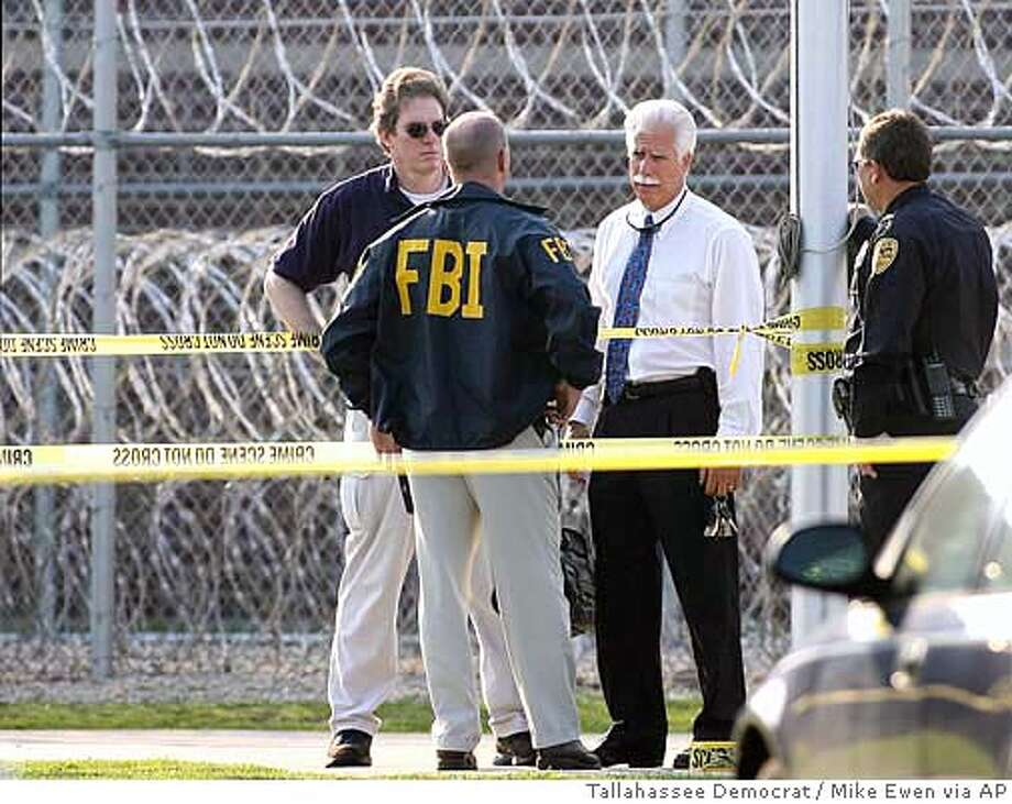** CORRECTS TO PELLEGRINO, SECOND FROM RIGHT ** FBI Special Agent-In-Charge Matthew Pellegrino, second from right, talks with FBI agents following a shooting Wednesday, June 21, 2006, inside the Tallahassee Detention Center, which is part of the Tallahassee Federal Correctional Institution in Tallahassee, Fla. A federal detention center guard unexpectedly opened fire Wednesday on agents who came to arrest him and five other guards accused of bribing female inmates for sex or threatening them to keep quiet, officials said. The guard and an agent died in the shootout, and another person was injured. (AP Photo/Tallahassee Democrat, Mike Ewen) CORRECTS TO PELLEGRINO, SECOND FROM RIGHT Photo: MIKE EWEN