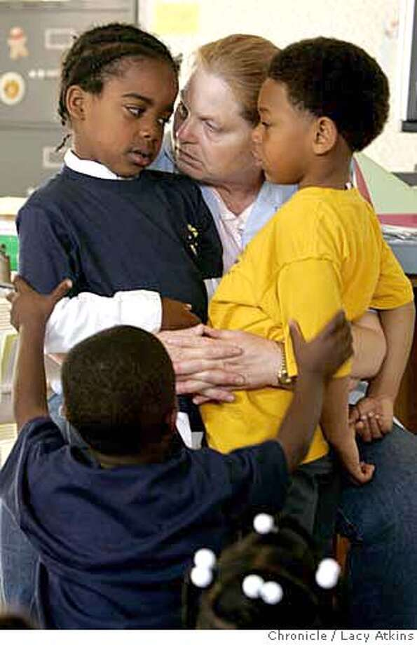 "Kindergarden teacher Ronda Beatty-Gallo, also known as ""Ms. B"" consoles Khalid Cross, left and Ja-von Kenard, right with th help of Stacy Tidwell, bottom, during class Tuesday June 13, 2006, at the Sankofa Academy in Oakland, Ca. The final days of the first year of the Sankofa Academy School in Oakland, Monday June 13, 2006, several of the teachers have decided not to return next year.  (Lacy Atkins/The Chronicle) Ran on: 06-22-2006  Teacher Ronda Beatty-Gallo, with Khalid Cross (left), Ja-von Kenard and Stacy Tidwell (center). Photo: Lacy Atkins"