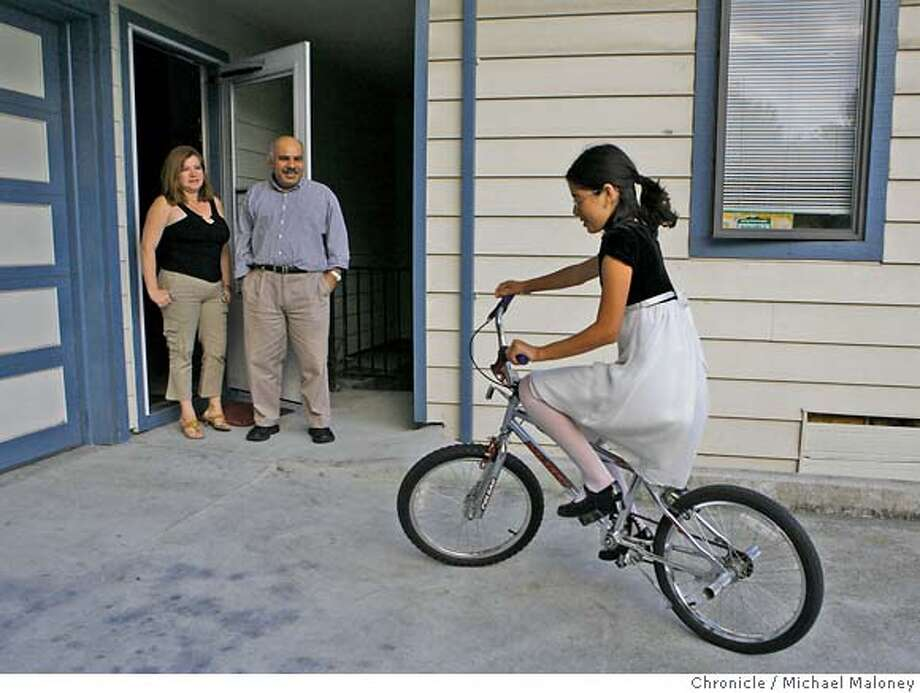 Irma and Alfonso Farfan watch their daughter Stephanie (11) pedal her bike in the driveway of their San Leandro, CA duplex. (They have one other child, Erick Farfan (16) who was not around for the photo shoot)  It took two years, thousands of dollars in fees and plenty of heartache before Alfonso Farfan was able to bring his wife and her children from El Salvador. After a year's wait, immigration authorities lost her paperwork and the couple had to start again from the beginning. Their story is unfortunately typical, and indeed, because Farfan is a U.S. citizen bringing in immediate family members, the process went much more quickly than it does for hundreds of thousands of others.  Photo by Michael Maloney / San Francisco Chronicle on 6/13/06 in San Leandro,CA **Alfonso, Irma, Stephanie and Erick Farfan MANDATORY CREDIT FOR PHOTOG AND SF CHRONICLE/ -MAGS OUT Photo: Michael Maloney