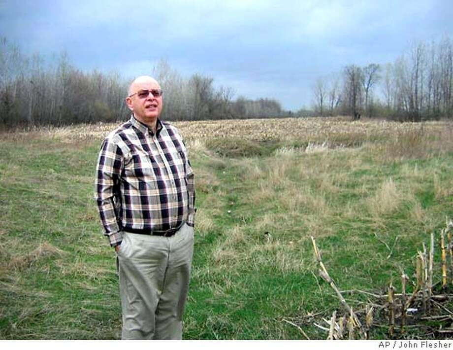 John Rapanos stands near his field in Michigan where his attempt to build a shopping mall was thwarted by the Clean Water Act. Associated Press photo, 2004, by John Flesher