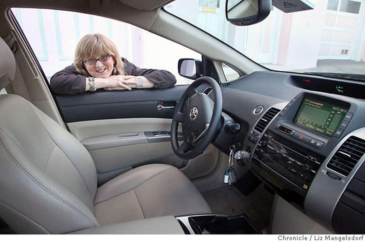 Marian Keeler peers into her Prius hybrid. For all its popularity, the car's interior environment makes the author wish a clean green car is around the corner. Chronicle photo by Liz Mangelsdorf