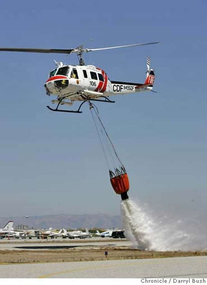 """A CDF helicopter based in Los Gatos performs a water drop, at the """"Vertical Challenge Helicopter Show,"""" held at Hiller Aviation Museum next to the San Carlos Airport in San Carlos, CA on Saturday, June 17, 2006. shot: 6/17/06  Darryl Bush / The Chronicle ** (cq) Photo: Darryl Bush"""