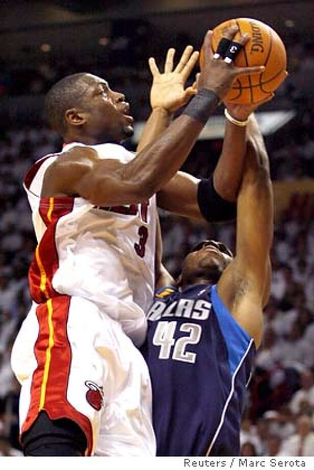Miami Heat's Dwyane Wade (L) goes up for a shot against Dallas Mavericks' defender Jerry Stackhouse during Game 3 of their NBA Finals basketball game in Miami June 13, 2006. REUTERS/Marc Serota (UNITED STATES) Photo: MARC SEROTA