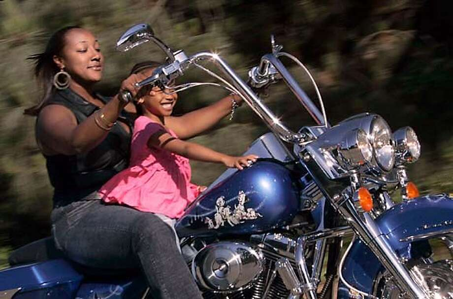 April Turner of Oakland and her 5-year-old goddaughter Akemi Williams sit on her motorcycle in the parking lot of the Oakland Zoo. Chronicle photo by Liz Hafalia