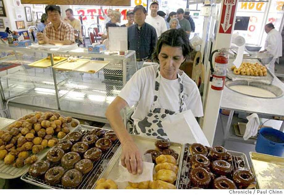Yolanda Molinari fills a customer's donut order. It was the last day for making donuts at Lou's Living Donut Museum in San Jose, Calif. on Saturday, June 10, 2006. The family-run business opened in 1955 and closed its doors for good due to an illness in the famly. Molinari is somehow hoping to reopen the donut shop some time in the near future.  PAUL CHINN/The Chronicle  **Yolanda Molinari MANDATORY CREDIT FOR PHOTOGRAPHER AND S.F. CHRONICLE/ - MAGS OUT Photo: PAUL CHINN