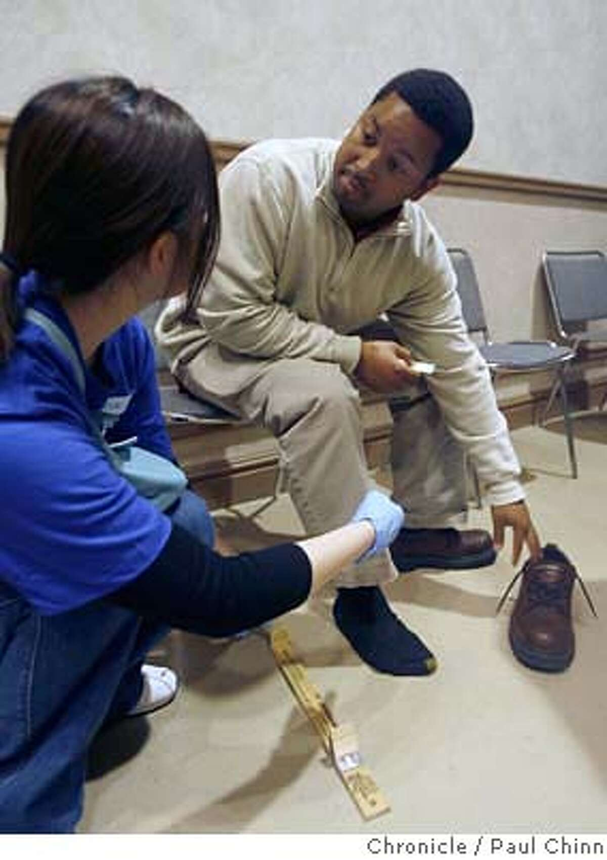 Corey Middleton (right) has his feet measured by a volunteer before receiving his free pair of shoes. More than 2,000 pairs of shoes were donated and given to homeless clients participating in the monthly Homeless Connect program at the Bill Graham Civic Auditorium in San Francisco, Calif. on Friday, June 9, 2006. PAUL CHINN/The Chronicle **Corey Middleton MANDATORY CREDIT FOR PHOTOGRAPHER AND S.F. CHRONICLE/ - MAGS OUT