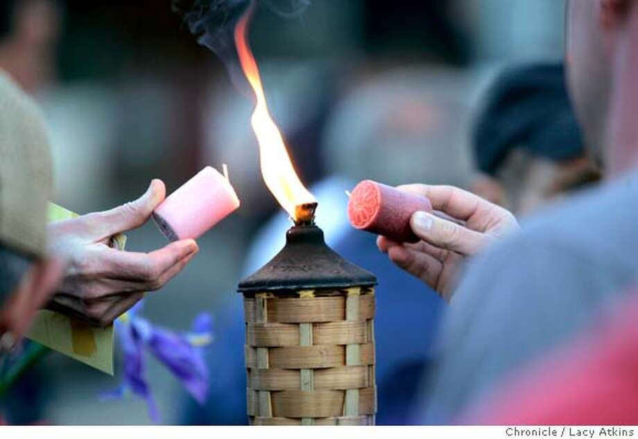 Hundreds of people share a flame to light their candles as the sunsets at the corner of Castro and Market, Sunday June 4, 2006 in San Francisco, Ca. People marched down Castro, which is known as ground zero 25 years ago for the AIDS virus in San Francisco, holding an Iris flower and a candle.  (Lacy Atkins/The Chronicle) MANDATORY CREDITFOR PHOTGRAPHER AND SAN FRANCISCO CHRONICLE/ -MAGS OUT Photo: Lacy Atkins