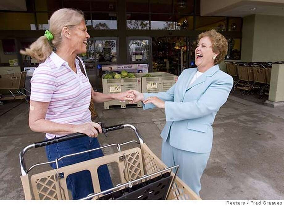 Democrat Francine Busby jokes with voter outside a supermarket in San Diego Photo: FRED GREAVES