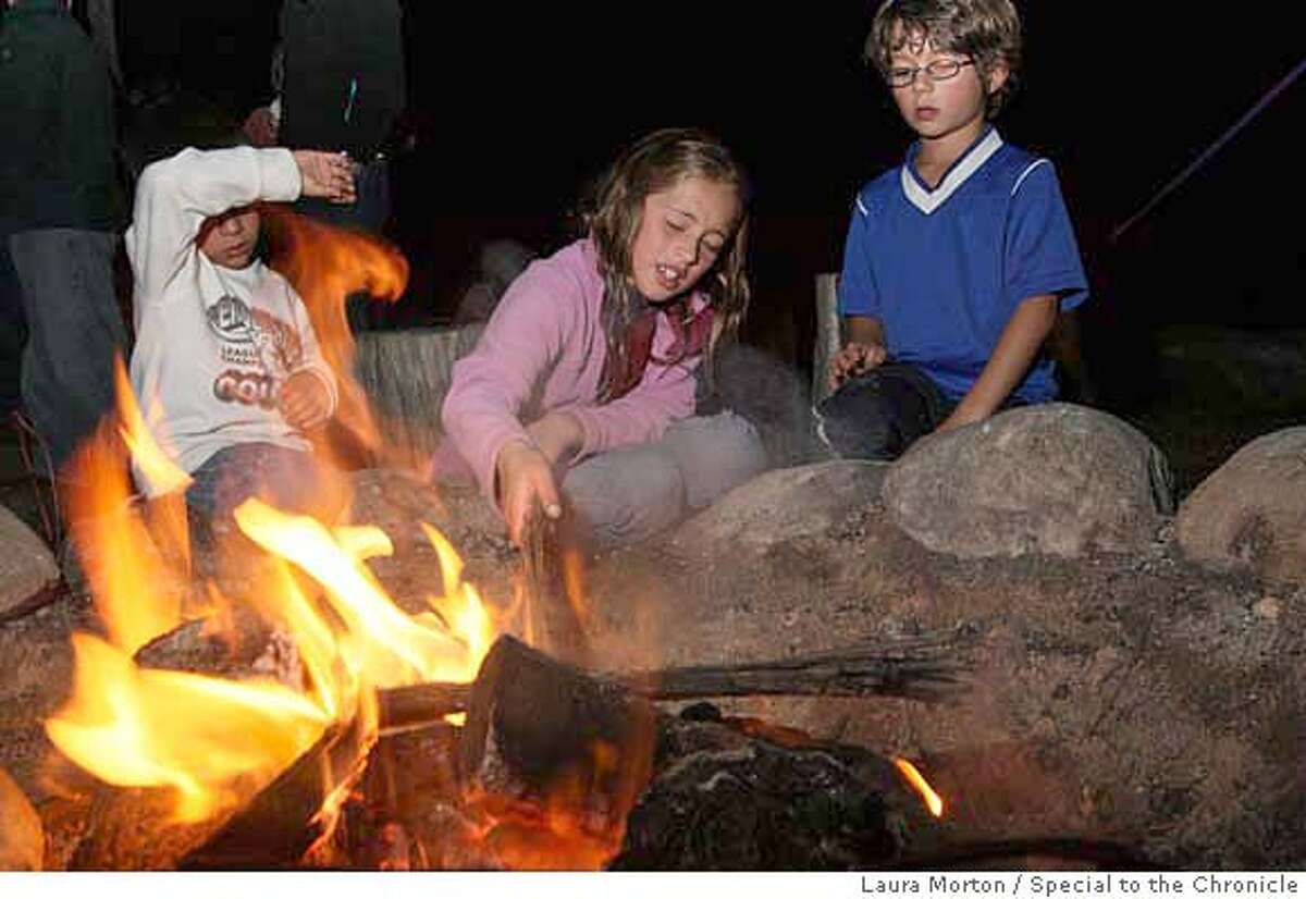 PARKS_KIDS22_0101_LKM.jpg Jordan Pineda, 9, (center) and Ellis Webb (right) play with the fire during a family campfire program at Rob Hill Campground in the Presidio. The campfire, organized by the Crissy Field Center, offered families a chance to make s'mores, listen to stories from park rangers and sing campfire songs. (Laura Morton/Special to the Chronicle) *** Jordan Pineda *** Ellis Webb