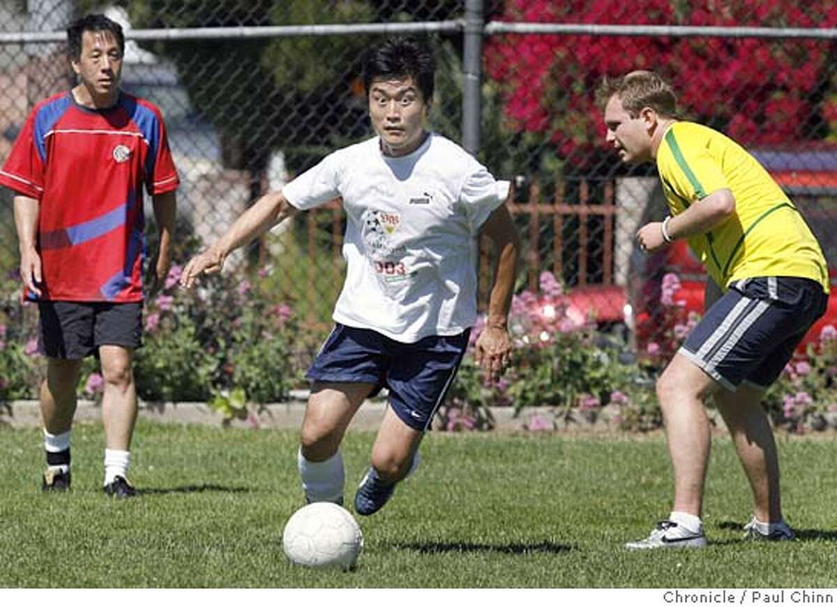 Peter Oh dribbles past Donavan Tom (left) and Onur Kaya (right) during a weekly pick-up game at a park in Berkeley, Calif. on Saturday, June 3, 2006. Soccer fans around the Bay Area are gearing up for the World Cup tournament which is about to begin in Germany later this month. PAUL CHINN/The Chronicle **Peter Oh, Donavan Tom, Onur Kaya
