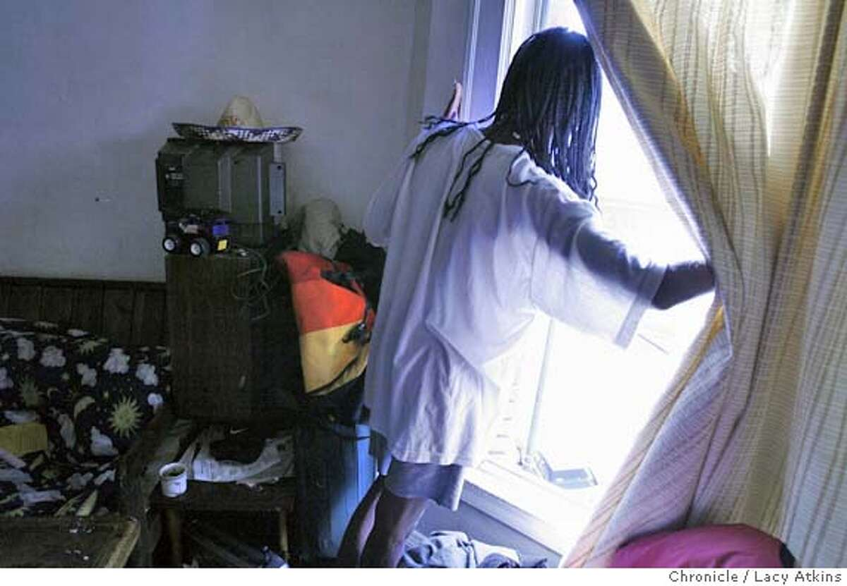 DeShawn Patton checks the weather from the window of her apartment at the Edgewurth Hotel in San Francisco's tenderloin. DeShawn Patton and boyfriend Carlos both have AIDS and live in the Edgewurth Hotel in San Francisco, MAy 4, 2006.Photo By Lacy Atkins