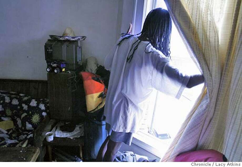 DeShawn Patton checks the weather from the window of her apartment at the Edgewurth Hotel in San Francisco's tenderloin. DeShawn Patton and boyfriend Carlos both have AIDS and live in the Edgewurth Hotel in San Francisco, MAy 4, 2006.Photo By Lacy Atkins Photo: Lacy Atkins