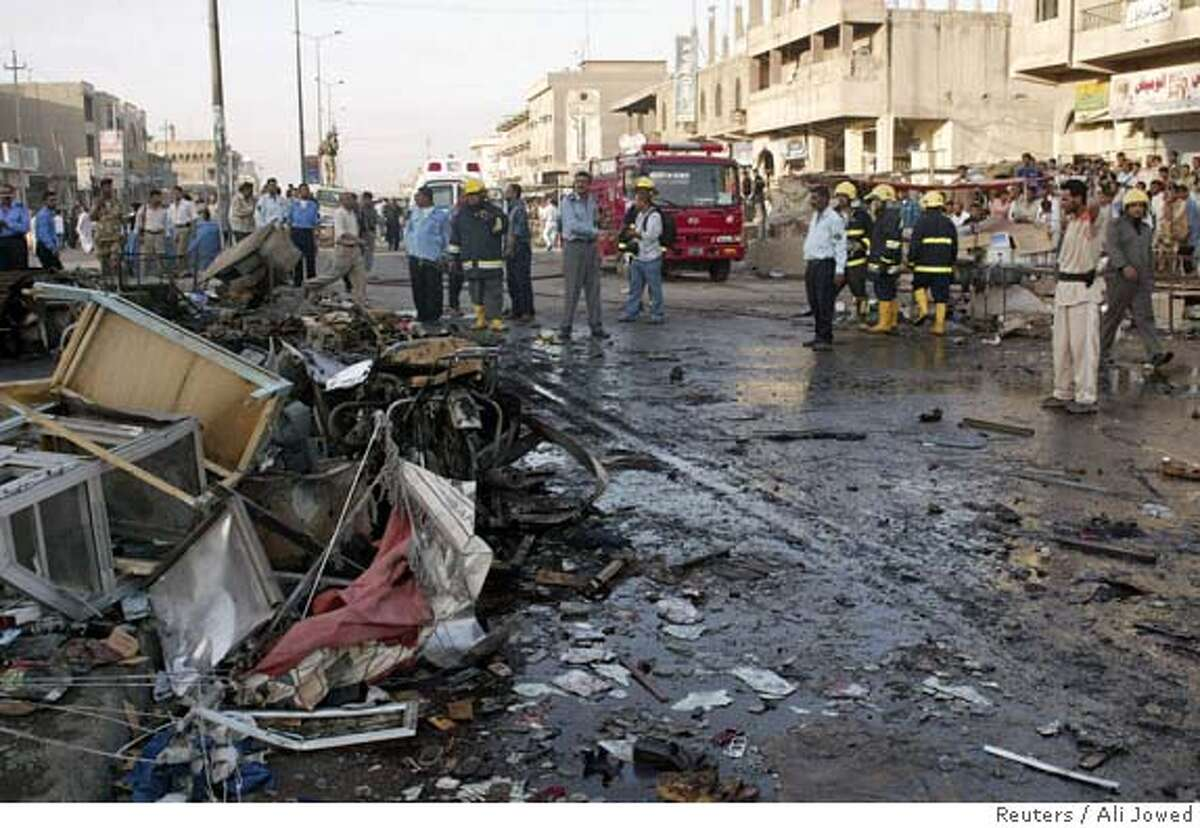 Bystanders look at the scene of a bombing which killed 15 people in Basra