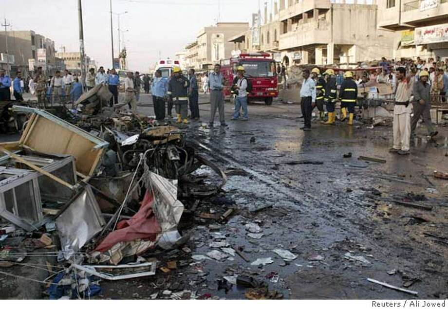 Bystanders look at the scene of a bombing which killed 15 people in Basra Photo: STRINGER/IRAQ