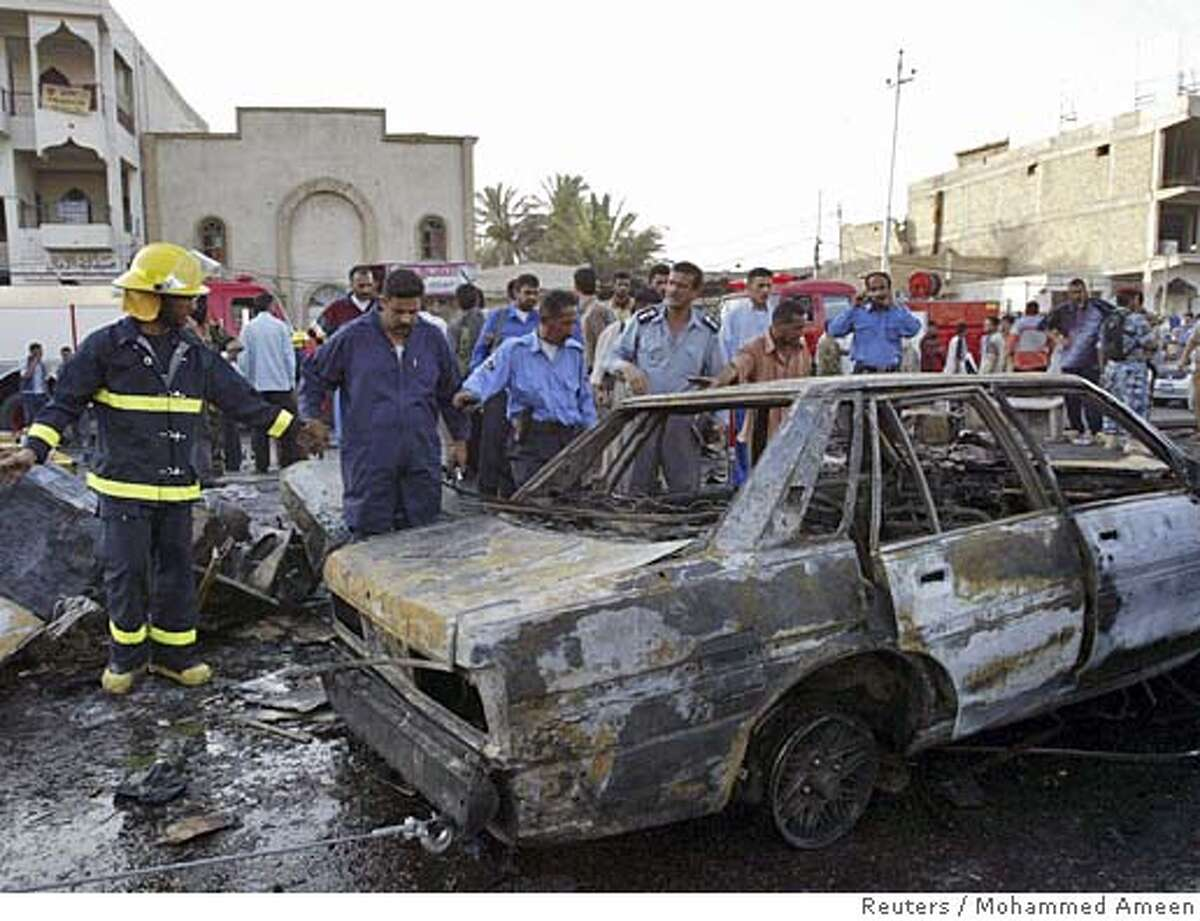 Iraqi police and firefighters remove a car from the scene of a bombing in Basra