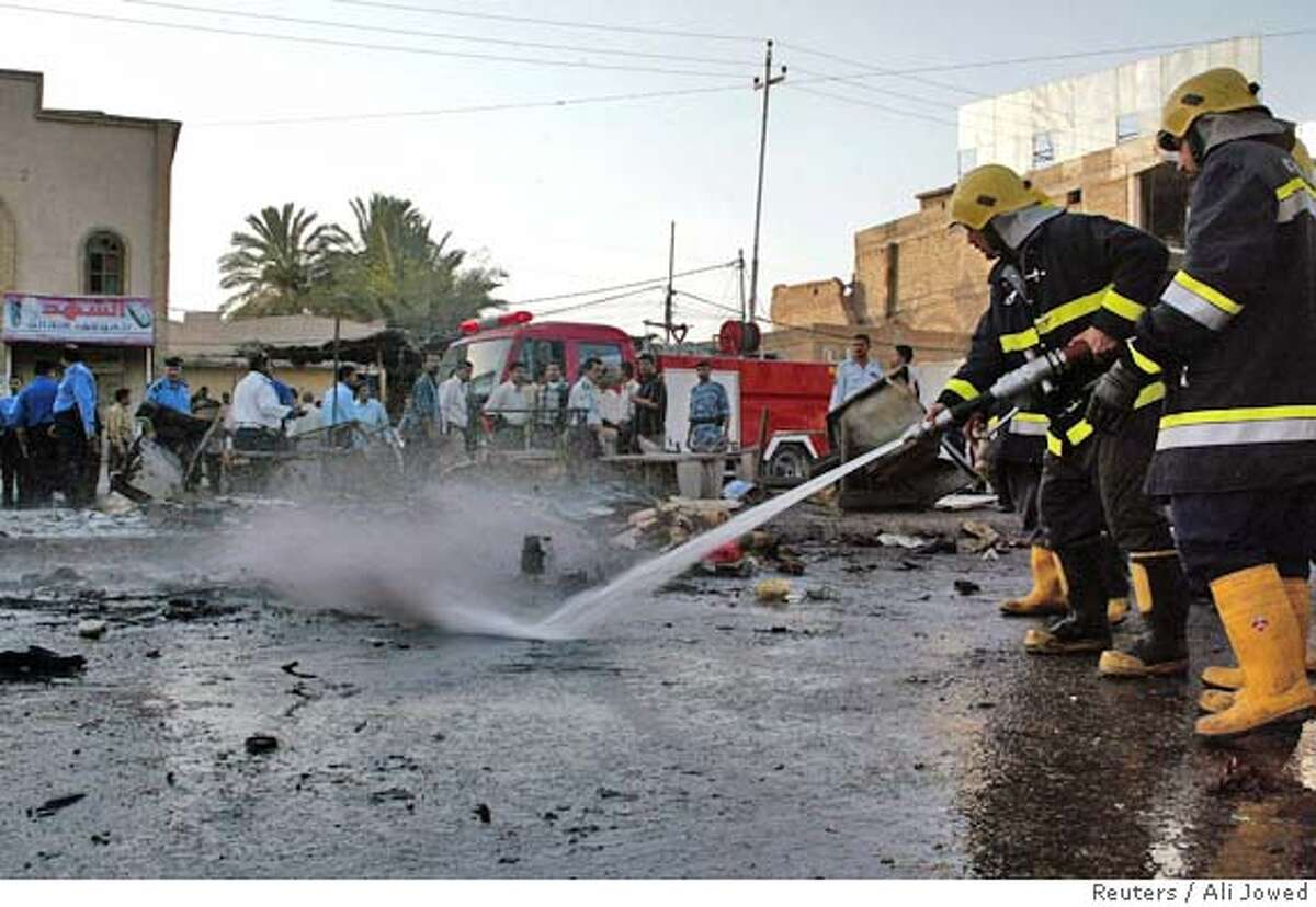 Iraqis firefighters wash the scene of a bombing which killed 15 people in Basra, 550 Km (341miles) south of Baghdad, June 3, 2006. REUTERS/Ali Jowed (IRAQ)