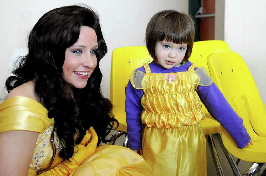 Grace Shiel, 3, experiences a sudden bout of shyness as she meets Belle, played by Julia Capogrossi, after Trinity Catholic students performed a preview of their upcoming show