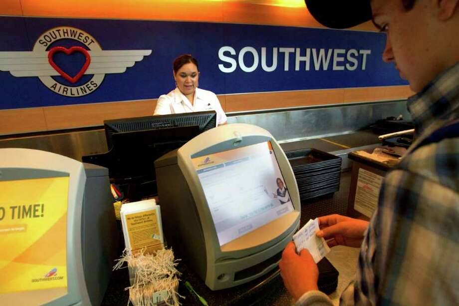 Southwest Airlines ticketing agent Amy Jackson, left, checks in customers last week at William P. Hobby Airport. Southwest is seeking the city's approval to build a new international terminal at the airport in south Houston. Photo: Cody Duty / © 2011 Houston Chronicle