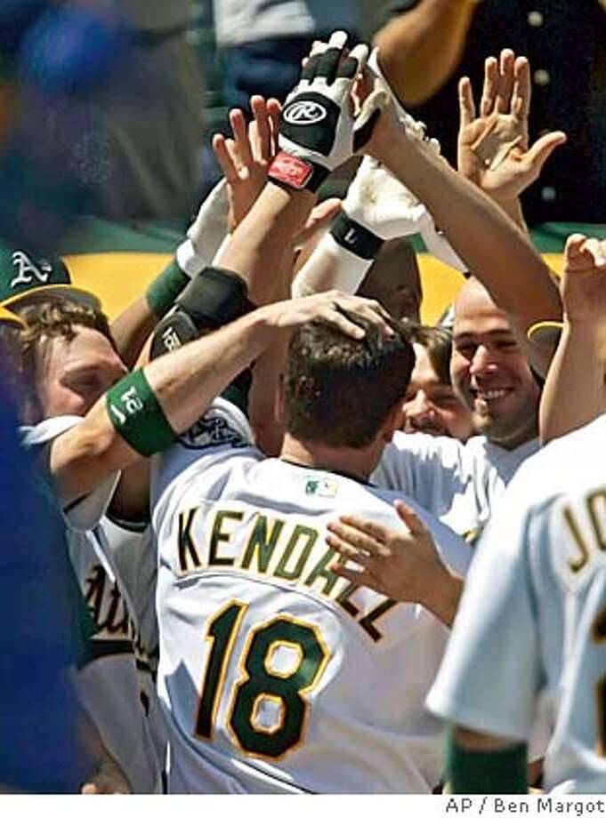 Oakland Athletics' Jason Kendall is mobbed in the dugout after hitting his first home run as an Athletic in the eighth inning of a baseball game, off Kansas City Royals' Joel Peralta, Wednesday, May 31, 2006 in Oakland, Calif. The A's won, 7-0. (AP Photo/Ben Margot) Photo: BEN MARGOT