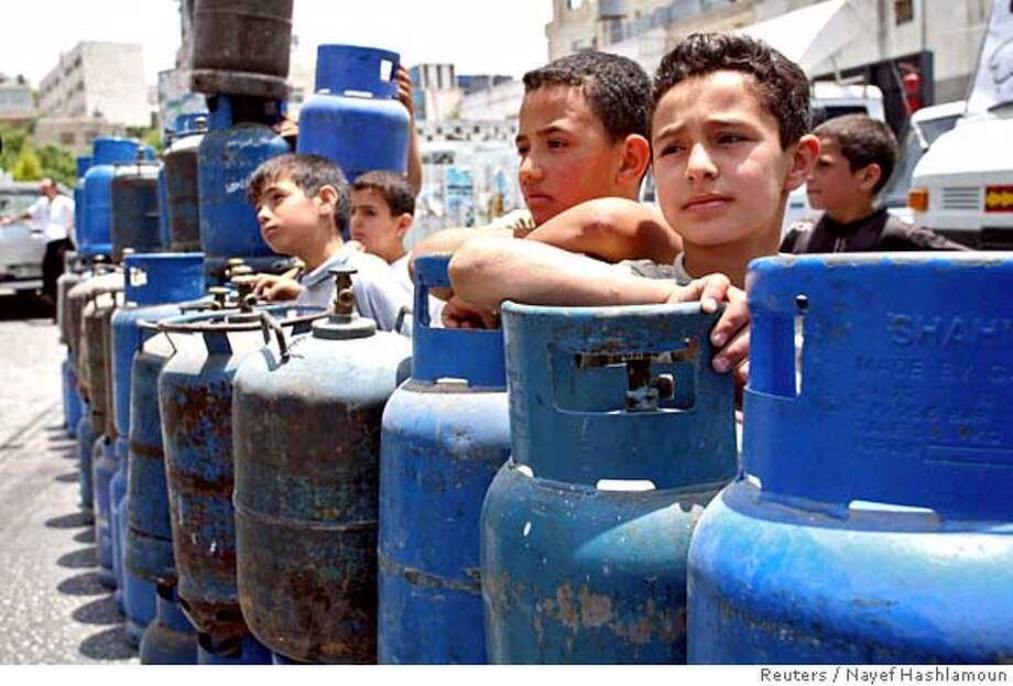 Palestinian boys stand next to empty gas containers during a protest in Hebron Photo: NAYEF HASHLAMOUN