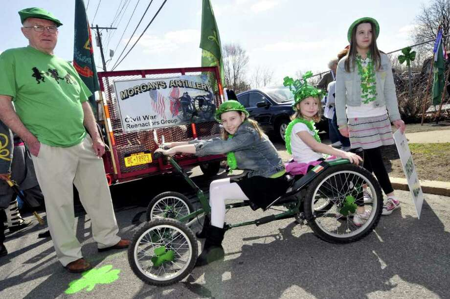 Joe Fitzgerald,left, lets his granddauagters Grace Fitzgearld, 11-years old, and Catherine Fitzgearld,5-years-old, sit on his Irish Mail quadricycle prior to the start of the North Albany Limericks 62nd annual St. Patrick?s Parade in Albany, NY Saturday March 17, 2012. Granddaughter Madeline,11-years-old, is right.( Michael P. Farrell/Times Union ) Photo: Michael P. Farrell