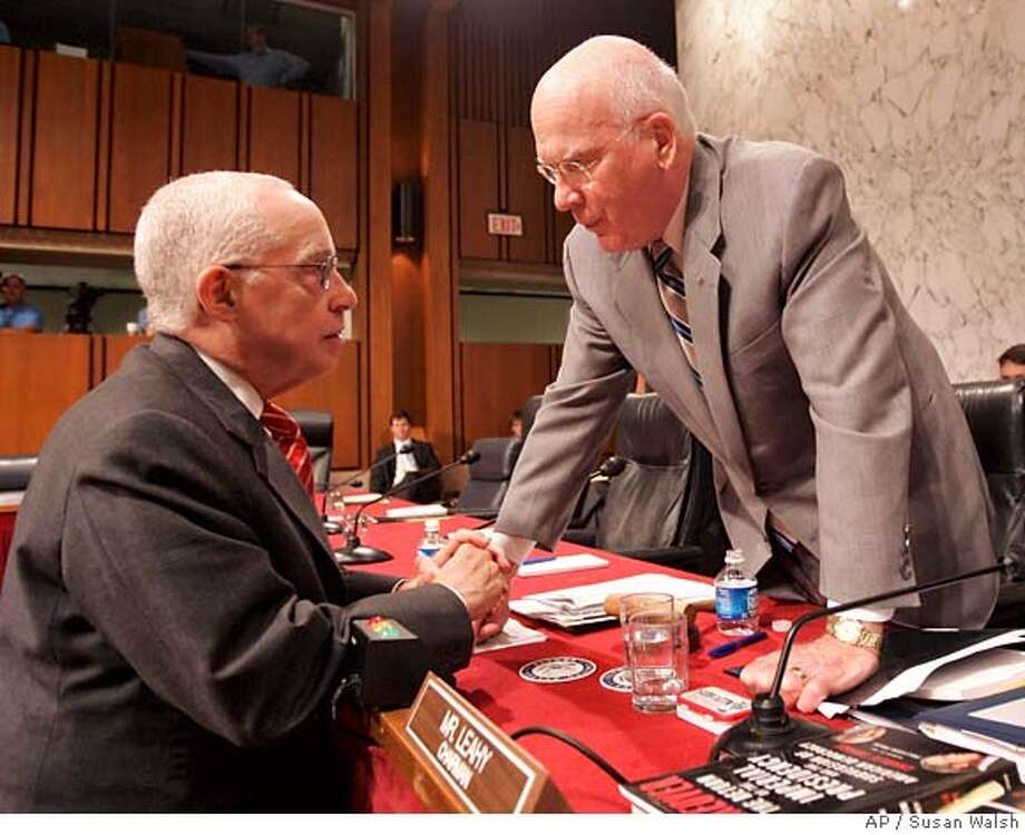 Senate Judiciary Committee Chairman Sen. Patrick Leahy, D-Vt., right, talks with Attorney General-designate Michael Mukasey on Capitol Hill in Washington, Thursday, Oct. 18, 2007, following Mukasey's second day of testifying before the committee's hearing on his nomination. (AP Photos/Susan Walsh) Photo: Susan Walsh