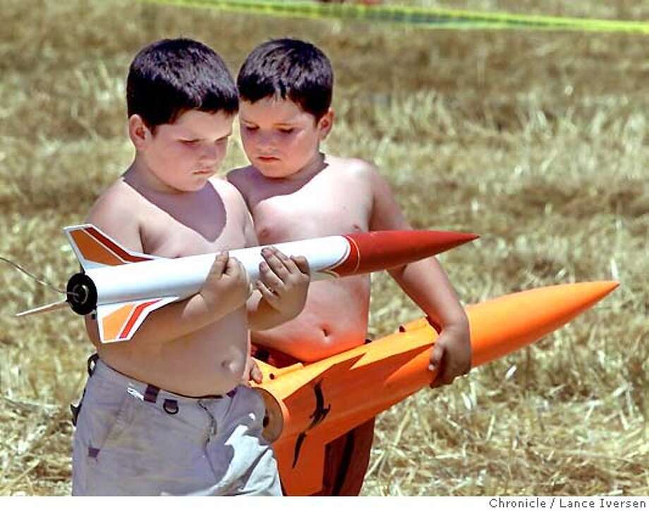 ROCKETSXX-06-C-19MAY01-MT-LI  Big boys and their toys: six year old twins L to R Anthony and Jonathan Meharg from Salinas, make their way to the starters table saturday. Model rocketry buffs from all over Northern Calif, gathered in Fresno 5/19/01 for the annual Dairy Aire High Powered model rocket try launch. By LANCE IVERSEN/SAN FRANCISCO CHRONICLE Photo: LANCE IVERSEN
