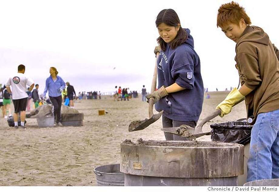 SAN FRANCISCO, CA - SEPTEMBER 15: Barbara Lau, 23 and Dylan Tong, 14 clean out a fire pit as they join in with hundreds of people as they clean the beach at Ocean Beach September 15, 2007 in San Francisco, California. (Photo by David Paul Morris/The Chronicle) Photo: David Paul Morris