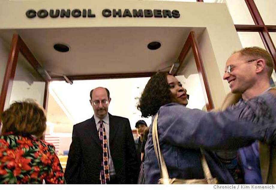 Hercules resident Brenda Smith Johnson, center hugs activist Jason Akel, right, as WalMart Attorney Edward Burg left, of Manatt,Phelps and Phillips exits the Hercules City Council chambers May 23 after the council voted to use a resolution of necessity, to use eminent domain to halt the construction of a planned WalMart Store there. Kim Komenich / The Chronicle  **L to R AP; herself; Steve Kirby MANDATORY CREDIT FOR PHOTOG AND SAN FRANCISCO CHRONICLE/ -MAGS OUT Photo: Kim Komenich