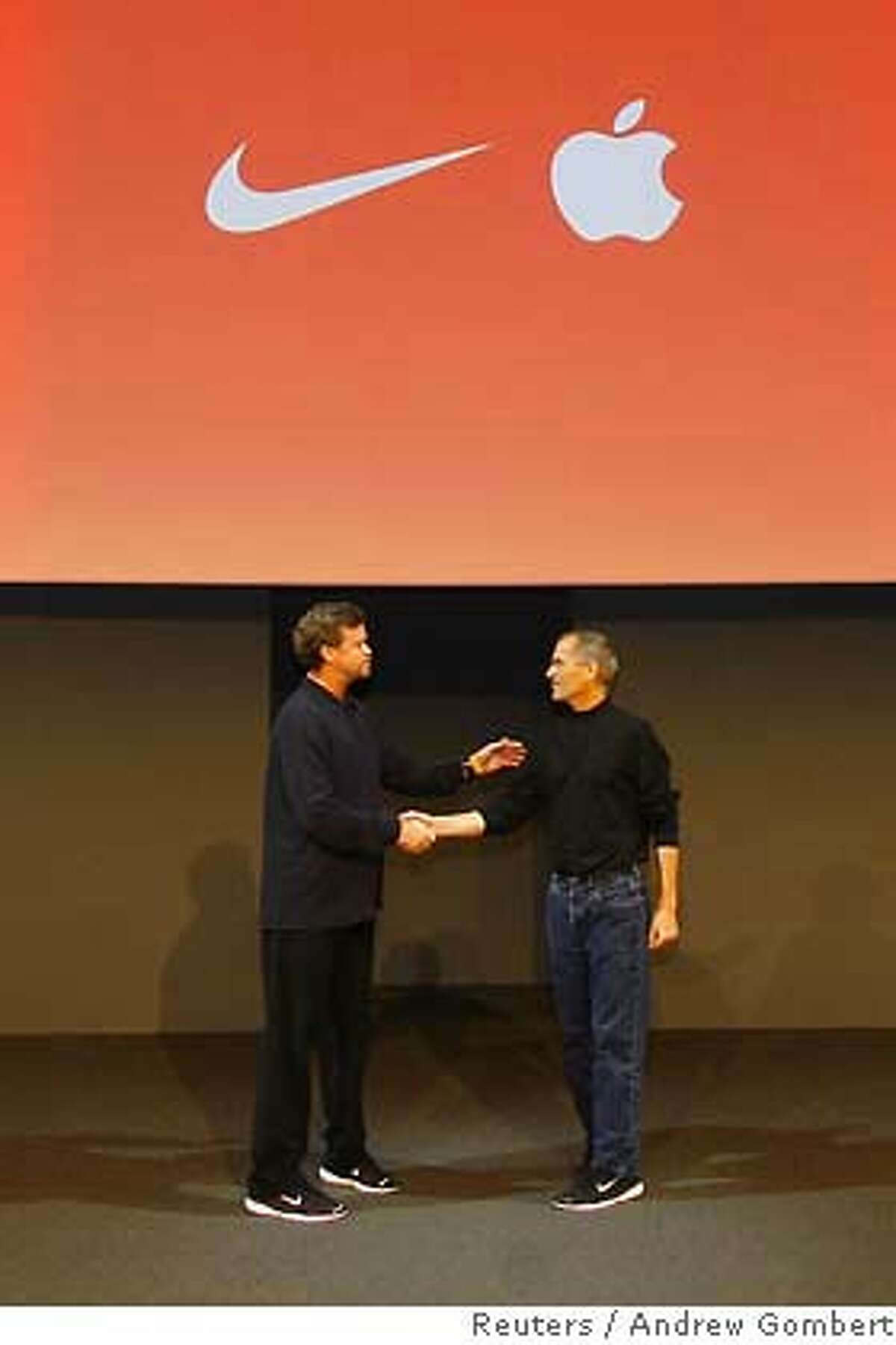 Nike CEO Parker (L) and Apple CEO Jobs shake hands at launch of their venture matching sneakers with ipod in New York