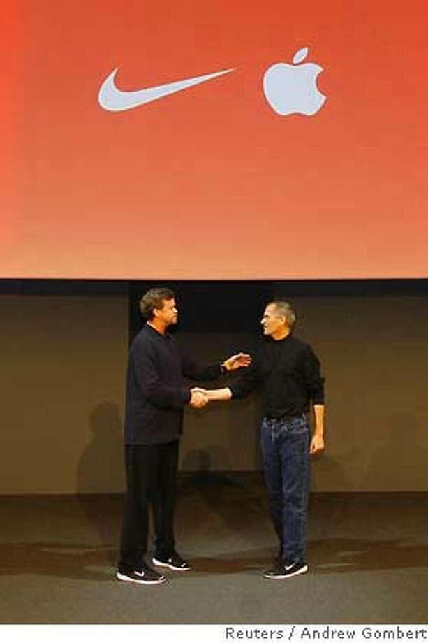 Nike CEO Parker (L) and Apple CEO Jobs shake hands at launch of their venture matching sneakers with ipod in New York Photo: HO
