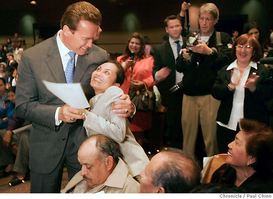 Mercy Ganas Prescott hugs Gov. Arnold Schwarzenegger after she was sworn-in as a United States citizen during a ceremony at the Masonic Auditorium in San Francisco, Calif. on Tuesday, May 23, 2006. Prescott, who lives in Foster City, came to the U.S. from the Philippines.  PAUL CHINN/The Chronicle  **Mercy Ganas Prescott, Gov. Arnold Schwarzenegger Photo: PAUL CHINN