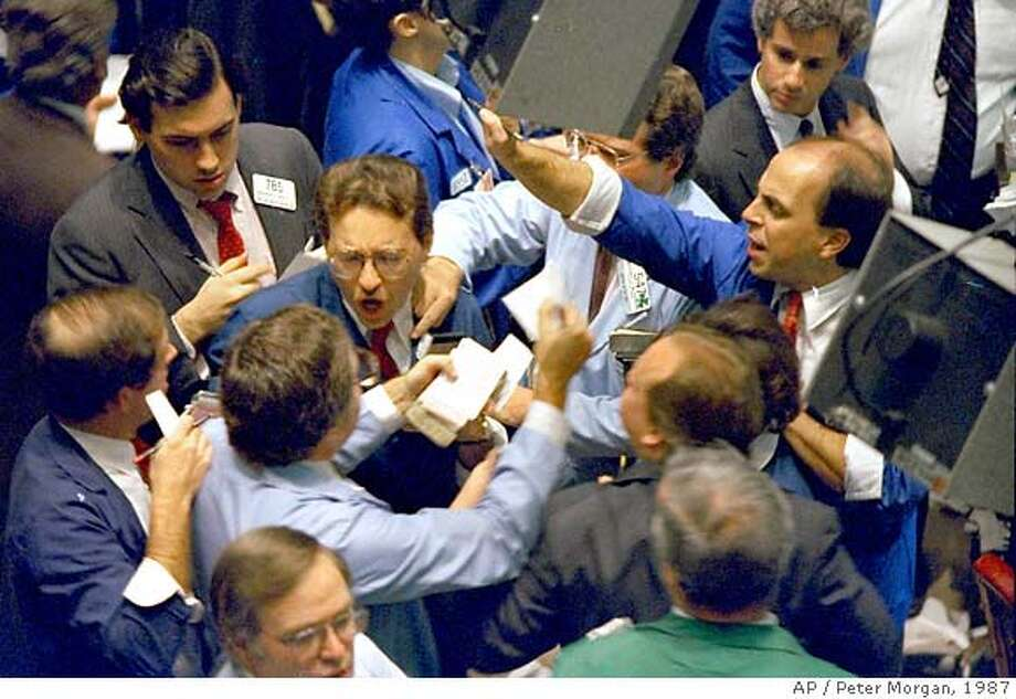 **FILE** Traders on the floor of the New York Stock Exchange work frantically as panic selling swept Wall Street in this Oct. 19, 1987 file photo. In the 20 years since one of Wall Street's worst crashes, the markets have grown bigger, more complex and faster. Investors have become increasingly aggressive, whether buying or selling. So while Wall Street was devastated by a 508-point plunge in the Dow Jones industrials on Oct. 19, 1987, a drop of that size today, while much smaller on a percentage basis, remains frightening. (AP Photo/Peter Morgan, File) Photo: PETER MORGAN