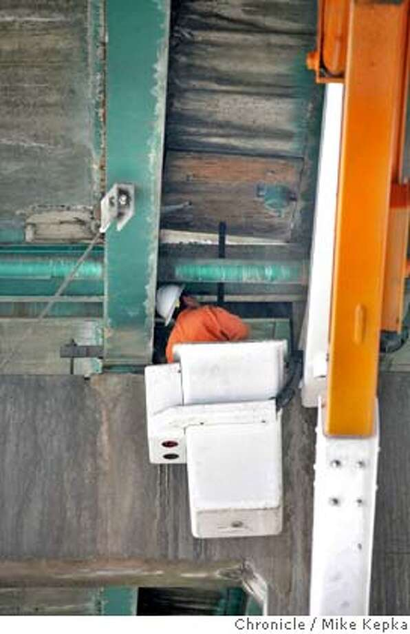 Underneath Interstate 880 northbound, CalTrans worker Jose Molina steadies a piece a plywood covering a sinkhole. The two right lanes of Northbound 880 at High Street were closed backing traffic for miles. Mike Kepka / The Chronicle Photo taken on 10/16/07, in Oakland, CA, USA Photo: Mike Kepka