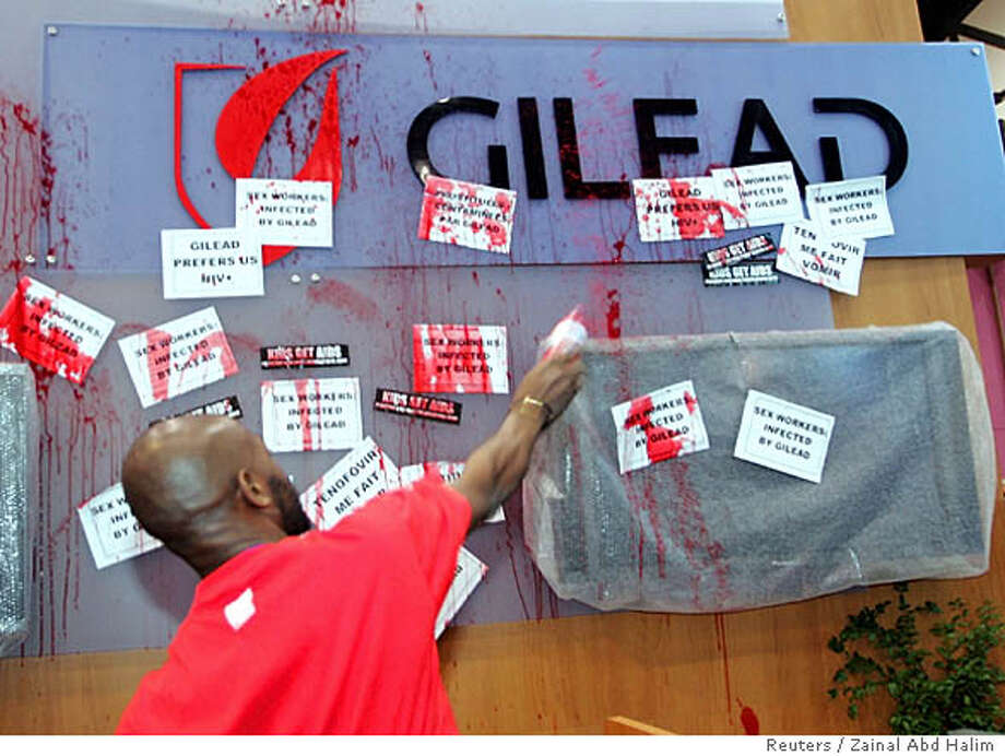 An activist throws paint in protest at a booth of a drug manufacturer during the 15th International AIDS Conference in Bangkok on July 14, 2004. The United States insists it is leading the global fight against AIDS despite stinging criticism of its drug and funding policies at a global conference. REUTERS/Zainal Abd Halim Ran on: 07-14-2004  An activist throws a can of paint at a booth of drug company Gilead Sciences during a protest at the Bangkok AIDS conference. 0 Photo: ZAINAL ABD HALIM
