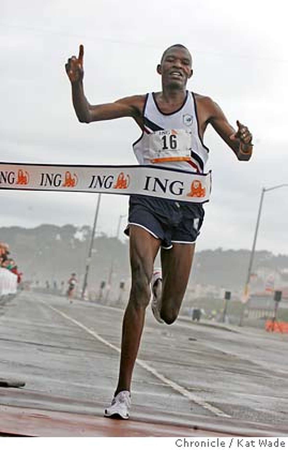 The defending champion, Gilbert Okari from Kenya takes first place in the Bay to Breakers as he crosses the finish line on the Great Highway at Ocean Beach about 35 minutes after the start of the 95th Annual Bay to Breakers race Sunday May 21, 2006. (Kat Wade/The Chronicle) ** Gilbert Okari cq