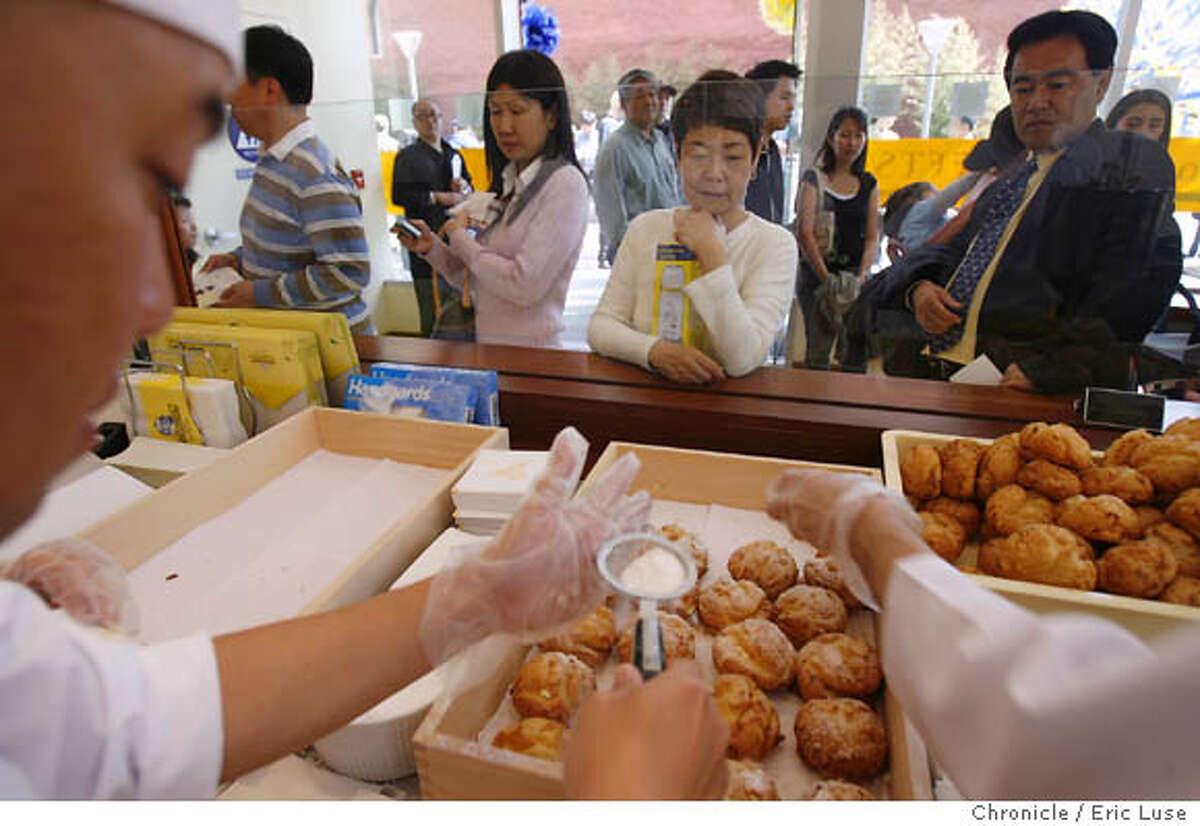 Mami Takada and Yoshiko Tsumura wait as Luigi Cruz puts the finishing touches on cream puffs at Beard Papa. Chronicle photo by Eric Luse