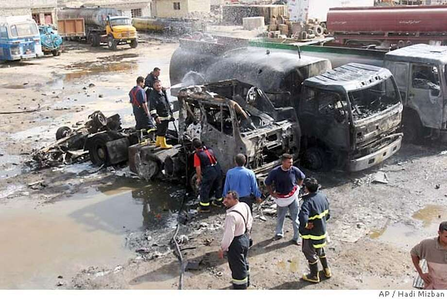Iraqi firefighters extinguish fire at trucks following an attack in Baghdad, Tuesday, May 16, 2006. Gunmen raided a parking area in a predominantly Shiite neighborhood of Baghdad Tuesday, shooting five people and killing at least 13 others when they triggered a car bomb, police said. (AP Photo/Hadi Mizban) Photo: HADI MIZBAN